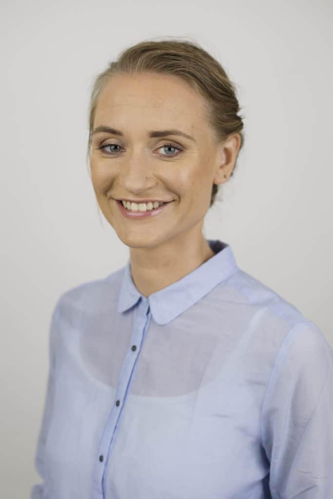 Portrait photo of role model Katja Dörlemann on grey background smiling into camera