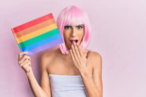 Young man with rainbow flag, pink wig and make-up; Young,Man,Wearing,Woman,Make,Up,Holding,Rainbow,Lgbtq,Flag