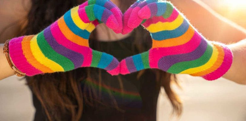 """Featured image of blogpost """"The Importance of Pronouns"""" showing two hands in rainbow-colored gloves making the heart symbol."""